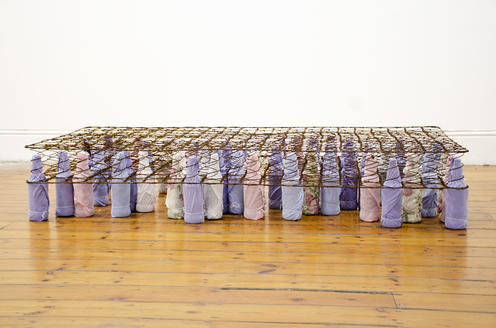 Lungiswa Gqunta, Let me ease the pain, 2016, Bed spring, beer bottles, bed linen and string, 90 x 190 cm. Courtesy the artist and Officine dell'Immagine